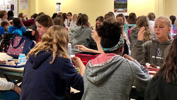 "HMS students eat lunch as they watch a live-stream presentation on the book ""A Long Walk to Water"". The presentation included the author and the main subject of the story."