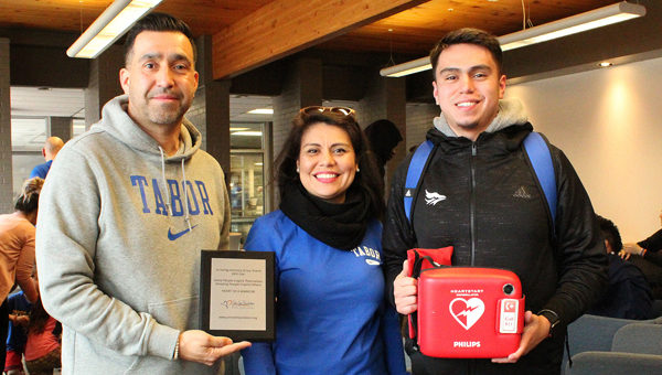 The Martinez family (Jason, Sandra and Nathan, from left) was on the Tabor College campus Saturday to donate an automated external defibrillator in honor of Nathan's best friend, John Lee, who died due to hypertrophic cardiomyopathy, a largely undetected disease that is the leading cause of death in student-athletes. Submitted Photo