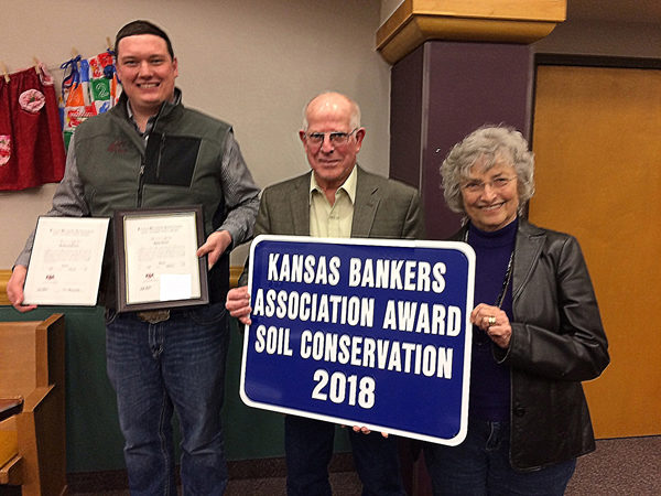 Tyler Ottensmeier, left, presents operator Rodney Suderman and sister Karen Penner of Newton the Kansas Bankers Association Award in Soil Conservation.  Patty Decker/Free Press
