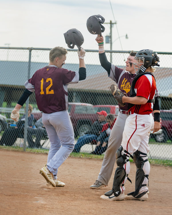 Hunter Hein and Brooks Gardner celebrate Hein's home run for the win over Hoisington. Karrie Rathbone/ Special to the Free Press