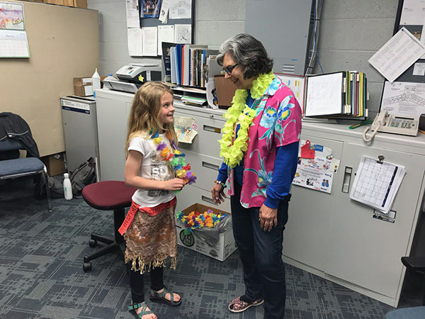 A Goessel Elementary student visits with retiring secretary Denise Nickel. Nickel has worked there for 25 years. Both were dressed up for a Hawaiian theme spirit day. Laura Fowler Paulus/Free Press