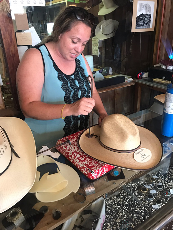 Johsie Reed custom brands a hat for her customer in her shop in Marion. She grew up in Marion County, but she learned the trade in California where she lived for several years. Laura Fowler Paulus/Free Press